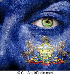 La bandera pintada en la cara con el ojo verde para mostrar el apoyo de Pennsylvania