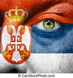 La bandera pintada en la cara con el ojo verde para mostrar el apoyo de Serbia