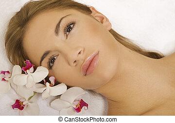 La bella cara de la joven bella mujer con flor