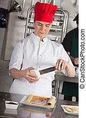 La chef femenina prepara un rollito de chocolate
