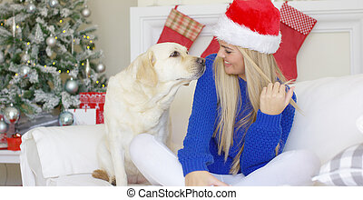 La chica de Navidad con su amigo perro en el sofá