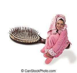 La chica de vestido rosa se sienta en un cepillo