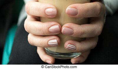La chica está sosteniendo una taza de café