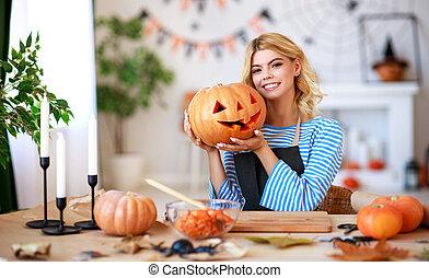 La chica feliz está cortando calabaza y se está preparando para Noche de Brujas