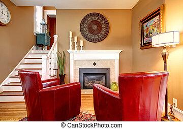 La clásica habitación familiar diseñada con cómodas sillas rojas, chimeneas de tonos ligeros, suelo de madera y paredes beige