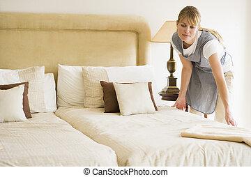 La criada haciendo la cama en la habitación del hotel