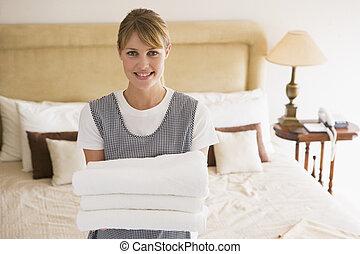 La doncella sosteniendo toallas en la habitación del hotel sonriendo
