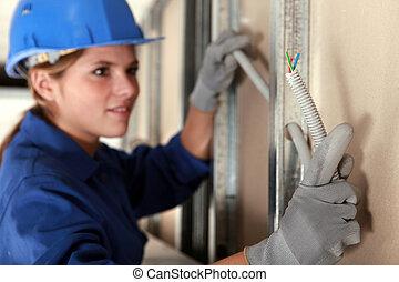 La encargada de instalar cables eléctricos