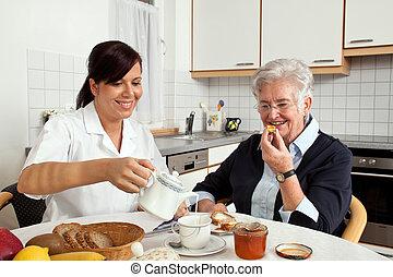 La enfermera ayuda a la anciana en el desayuno