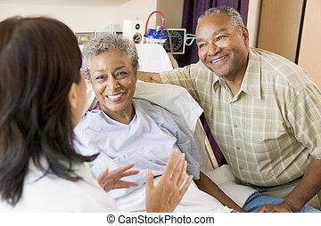 La enfermera hablando con la pareja mayor