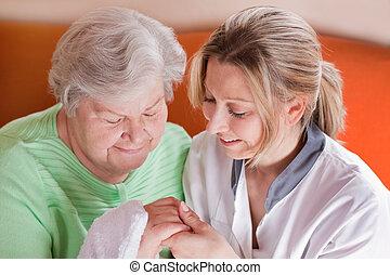 La enfermera lava las manos de una anciana