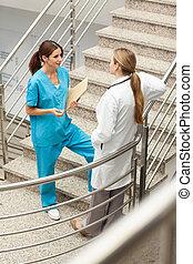 La enfermera y el doctor hablando juntos en una escalera
