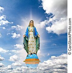 La estatua de la Virgen María en el fondo del cielo.