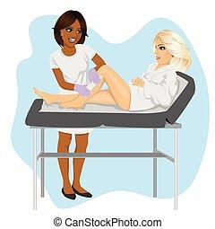 La esteticista afroamericana depilando las piernas de una joven rubia en una cama de spa