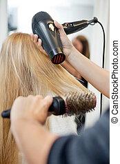 La estilista secando el pelo de la mujer en la peluquería