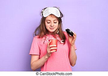 La estudiante mira dentro de una taza de papel, se pregunta cuánto café queda