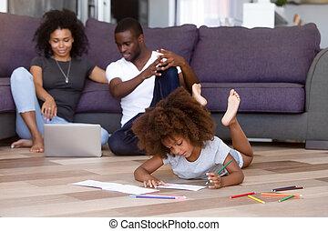 La familia africana pasa tiempo en casa sentada en el suelo caliente