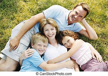 La familia al aire libre sonríe