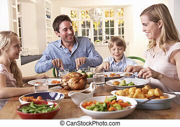 La familia feliz cenando pollo asado en la mesa