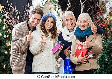 La familia feliz gestando pulgares en la tienda de Navidad