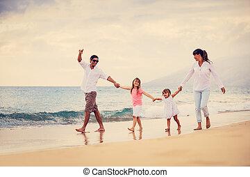 La familia feliz se divierte caminando por la playa al atardecer