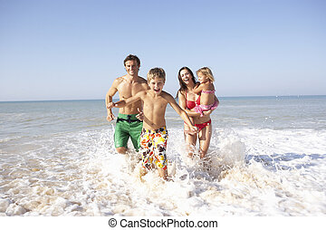 La familia joven juega en la playa