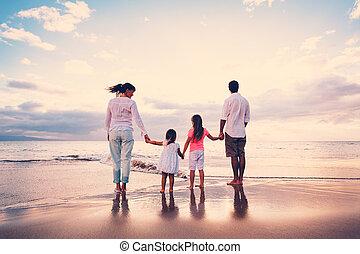 La familia se divierte en la playa al atardecer
