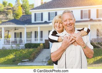 La feliz pareja de ancianos en el patio delantero de la casa