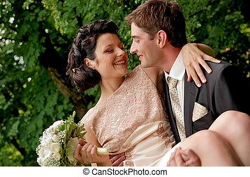 La feliz pareja de bodas sonriente al aire libre.