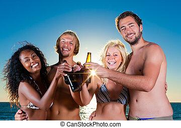 La gente da una fiesta en la playa con bebidas