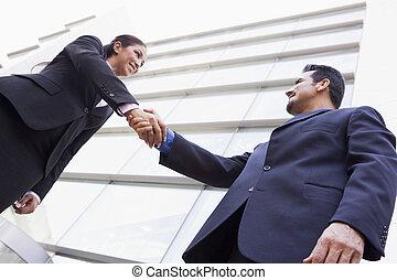 La gente de negocios da la mano fuera de la oficina