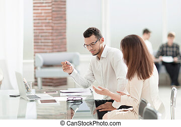 La gente de negocios discute algo sentado en la mesa de la oficina