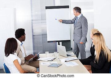 La gente de negocios mira a los hombres explicando