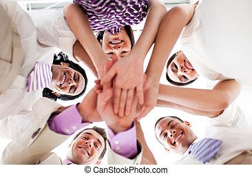 La gente de negocios sonriente se toma de la mano en un círculo