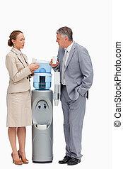 La gente de traje hablando al lado del dispensador de agua