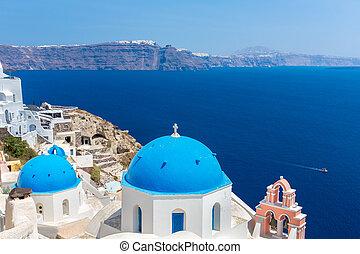 La iglesia más famosa de la isla Santorini, Creta, Grecia. Bell Tower y Cupolas de la clásica iglesia griega ortodoxa con vista al mar Mediterráneo y la isla Spinalonga