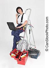 La joven artesana con portátil y herramientas misceláneas