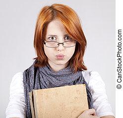 La joven chica de la moda en vasos con un libro viejo