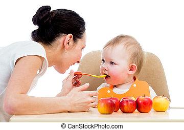 La joven madre alimentando a su niña