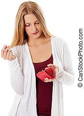 La joven muestra su billetera vacía. Bancarrota