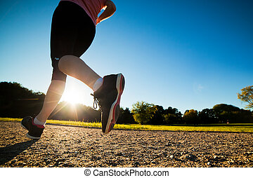 La joven mujer en forma corre, entrenando