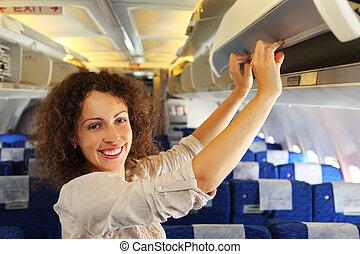 La joven mujer hermosa en el avión añade equipaje, filas de asientos azules
