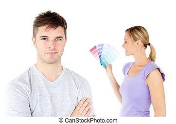 La joven pareja caucásica escogiendo colores para pintar su habitación