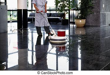La limpiadora de adultos con un pasillo de limpieza uniforme