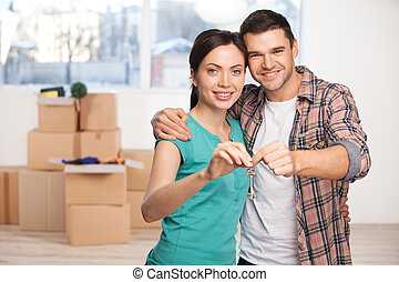 La llave de su nueva casa. Una feliz pareja joven parada cerca de la otra y sonriendo mientras sostenía la llave de la casa