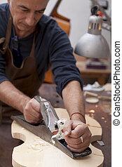 La lutemaker de Artisan trabajando en un violín en su taller
