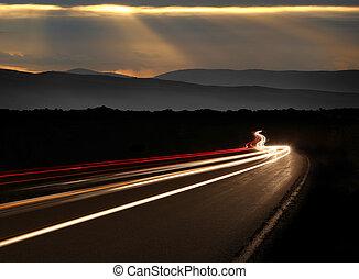 La luz de la noche del auto se va por las montañas