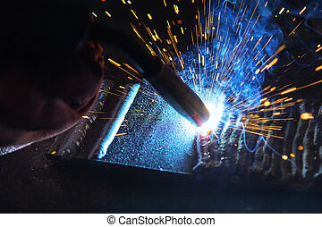 La luz de la soldadura en la escena de cerca, la antorcha de la máquina de soldar con la luz de la chispa en azul
