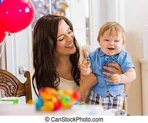 La madre reteniendo al niño en la fiesta de cumpleaños