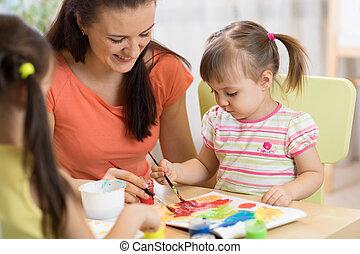 La maestra y las niñas están pintando en la guardería. La mujer y los niños tienen un pasatiempo divertido.
